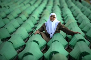 A Bosnian woman mourns over coffins of a