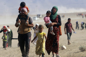 Displaced people from the minority Yazidi sect, fleeing violence from forces loyal to the Islamic State in Sinjar town, walk towards the Syrian border, on the outskirts of Sinjar mountain, near the Syrian border town of Elierbeh of Al-Hasakah Governorate August 11, 2014. Islamic State militants have killed at least 500 members of Iraq's Yazidi ethnic minority during their offensive in the north, Iraq's human rights minister told Reuters on Sunday. The Islamic State, which has declared a caliphate in parts of Iraq and Syria, has prompted tens of thousands of Yazidis and Christians to flee for their lives during their push to within a 30-minute drive of the Kurdish regional capital Arbil. Picture taken August 11, 2014.      REUTERS/Rodi Said    (IRAQ - Tags: POLITICS CIVIL UNREST) CONFLICT)
